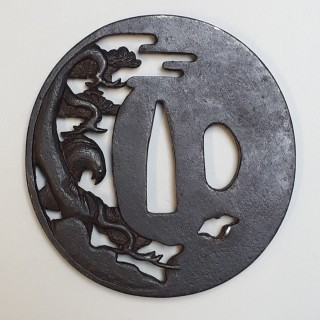 An antique Japanese iron tsuba decorated with a hawk