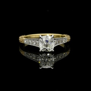 A charming 1.07ct old mine cushion cut solitaire ring in gold and platinum with diamond shoulders.