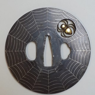 An antique Japanese tsuba decorated with a spider and web