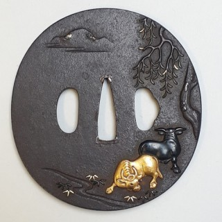 An antique Japanese iron tsuba with multimetal cow decoration