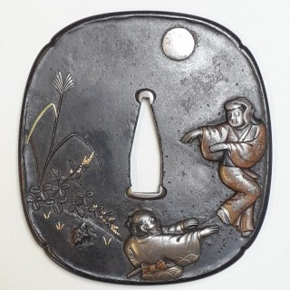 An antique Japanese iron tsuba decorated with a dancing couple