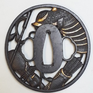 An antique Japanese iron tsuba with a cut out design of samurai effects