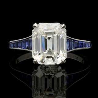 A beautiful and unusual 3.20ct emerald-cut diamond ring with calibre-cut sapphire band.
