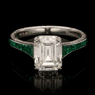 A 2.34ct emerald-cut diamond ring with ornately engraved platinum band set with emeralds.