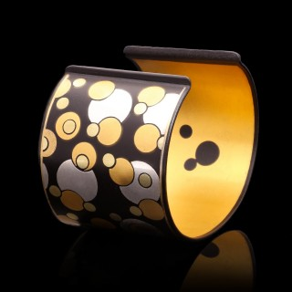 A gold, silver and iron 'Bubble' cuff bangle designed by Angela Cummings