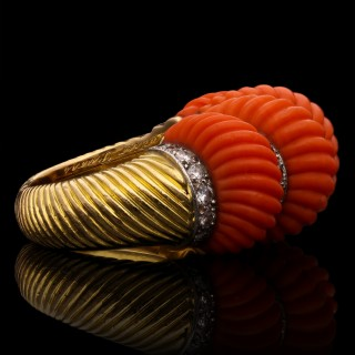 A striking and bold bombe-style dress ring set with carved coral and round brilliant cut diamonds.
