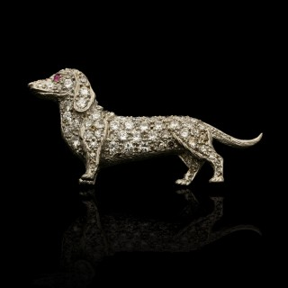 A charming platinum and pavé diamond brooch in the form of a Dachshund.