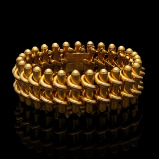 A striking wide gold antique strap bracelet of flexible interwoven bar design.