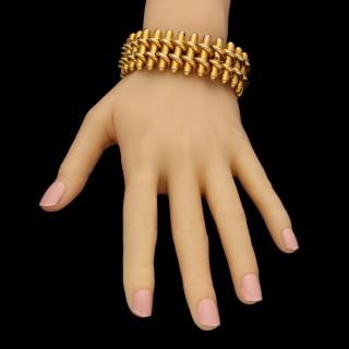 A striking wide gold antique strap bracelet of flexible interwoven bar design.