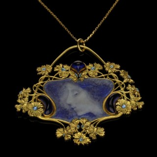 A beautiful antique gold and blue enamel pendant of a maiden in a cornflower surround. c.1900
