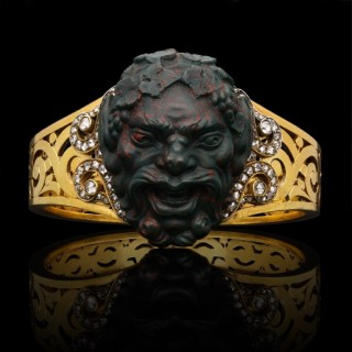 A magnificent pierced gold bangle set with the head of Bacchus finely carved in bloodstone. c.1880