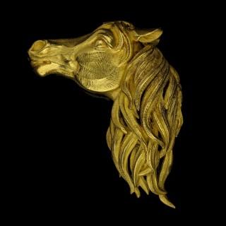 A stylish gold brooch realistically modelled as a three-dimensional horse's head.
