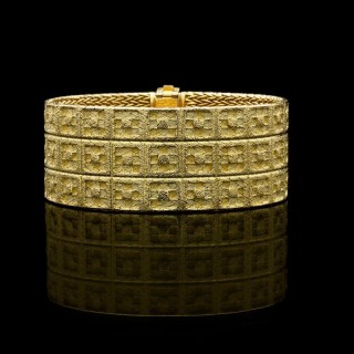A stylish strap bracelet designed as three rows of square motifs in textured 18ct yellow gold. c.1970's