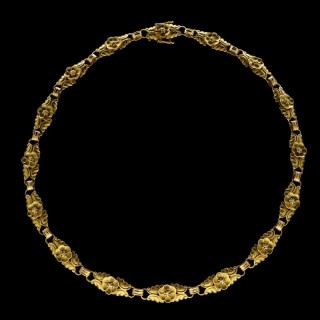 A lovely rare 18ct yellow gold necklace formed of matching links with flower and double leaf motifs.c.1935