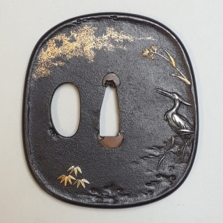 An antique Japanese iron tsuba decorated with a fishing egret