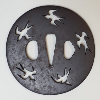 An antique Japanese iron tsuba decorated with a cut out design of birds