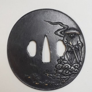 An antique Japanese iron tsuba with an image of shoki