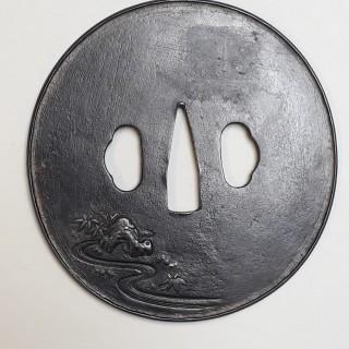 An antique Japanese iron tsuba with an image of shoki