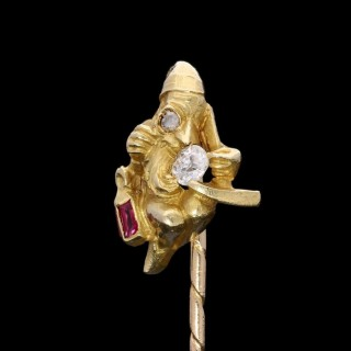 A delightful Victorian gold stick pin of a miner with ruby lamp and pick axe kneeling to examine a diamond. c.1890