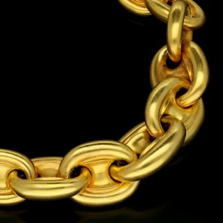 A gold anchor link chain necklace of graduated form with soft satinised finish.