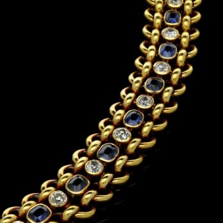 An 18ct yellow gold chain link bracelet with a central row of old-cut diamonds and sapphires.