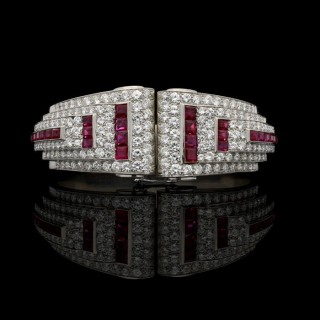 An Art Deco round diamond and square calibre ruby geometric hinged cuff bracelet in platinum.