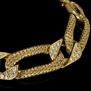 An 18ct yellow gold bracelet with textured elongated links alternating with diamond set links.