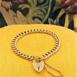 A very fine 18 Carat Yellow Gold (marked) Curb Link Bracelet with a Heart Shaped Padlock Closure. English,  Circa 1890.