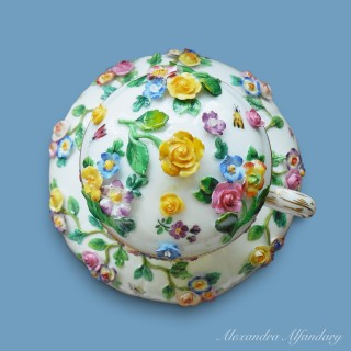 A Meissen Porcelain Chocolate Cup, Saucer and Lid, profusely decorated with applied flowers