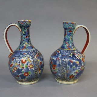 A pair of 17th century Japanese clobbered Arita porcelain ewers