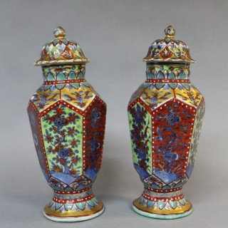 A pair of late 17th century Kang Hsi Chinese clobbered porcelain jars and covers of hexagonal form