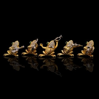 A delightful set of five gold and gem-set musical frog brooches each playing a different instrument.