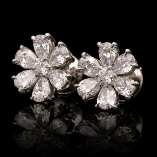 A beautiful pair of platinum and pear-shaped diamond flower head earrings.
