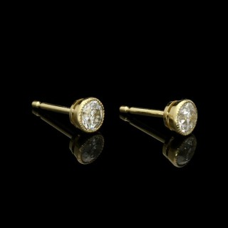 A pair of old-cut diamond stud earrings in yellow gold rub over settings with millegrain edging.