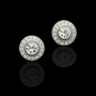 A pretty pair of old cut diamond and platinum ear studs with detachable diamond cluster jackets.