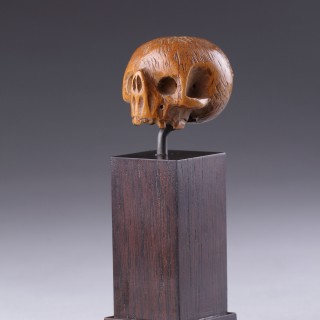 An Unusual South German Carved Boxwood Rosary Bead Depicting a Skull with a Deformed Nose