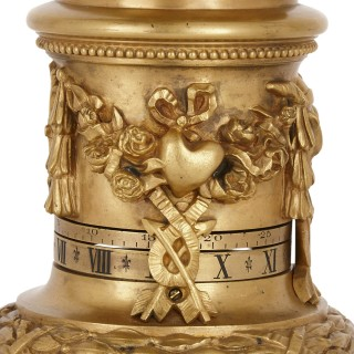 Gilt bronze cylindrical mantel clock with emblems of love