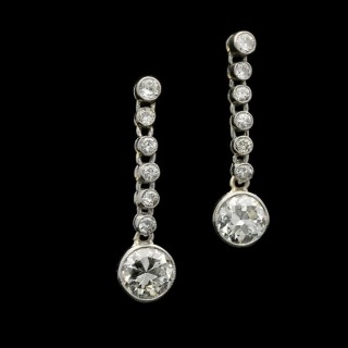 An elegant pair of diamond and platinum drop earrings in millegrain settings.