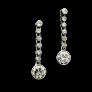 An elegant pair of diamond and platinum drop earrings in millegrain settings.
