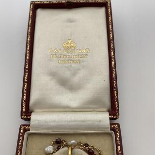 A Carlo Giuliano garnet, pearl and diamond pendant and chain.