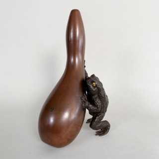 An amusing Bronze Okimono of a toad struggling with a gourd