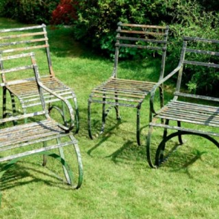 Set of four Regency period painted wrought iron garden chairs.