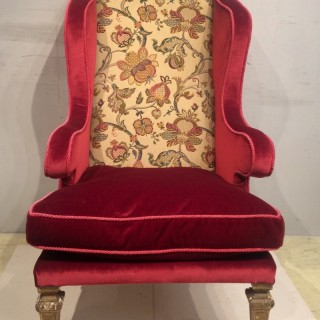 A 19th century well shaped carved giltwood wing armchair.