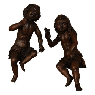 Two oak angels each holding a fig, Dutch late 17th century
