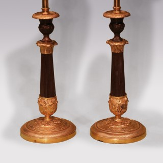 A pair of Regency period bronze and ormolu candlestick lamps