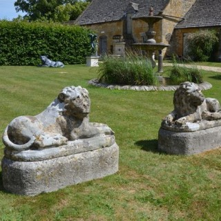 A pair of carved limestone recumbent lions