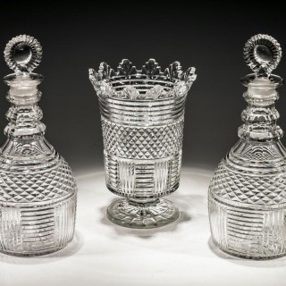 A PAIR OF DIAMOND & STEP CUT PANELLED REGENCY DECANTERS WITH MATCHING VANDYKE VASE