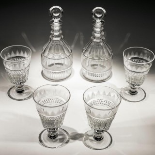 A SUITE OF CUT GLASS GEORGIAN DECANTERS AND DRINKING GLASSES