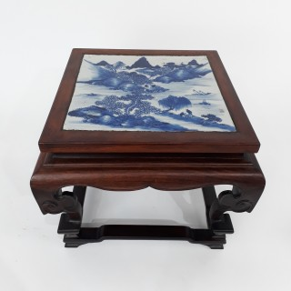 A small Chinese wood stand with blue and white porcelain panel