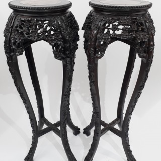 A pair of tall Chinese wood stands with marble tops